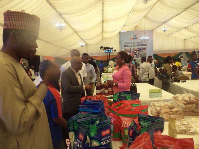 Government officials inspecting products on exhibit